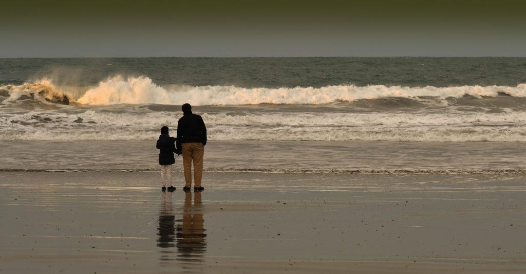 Père et sa fille devant l'océan