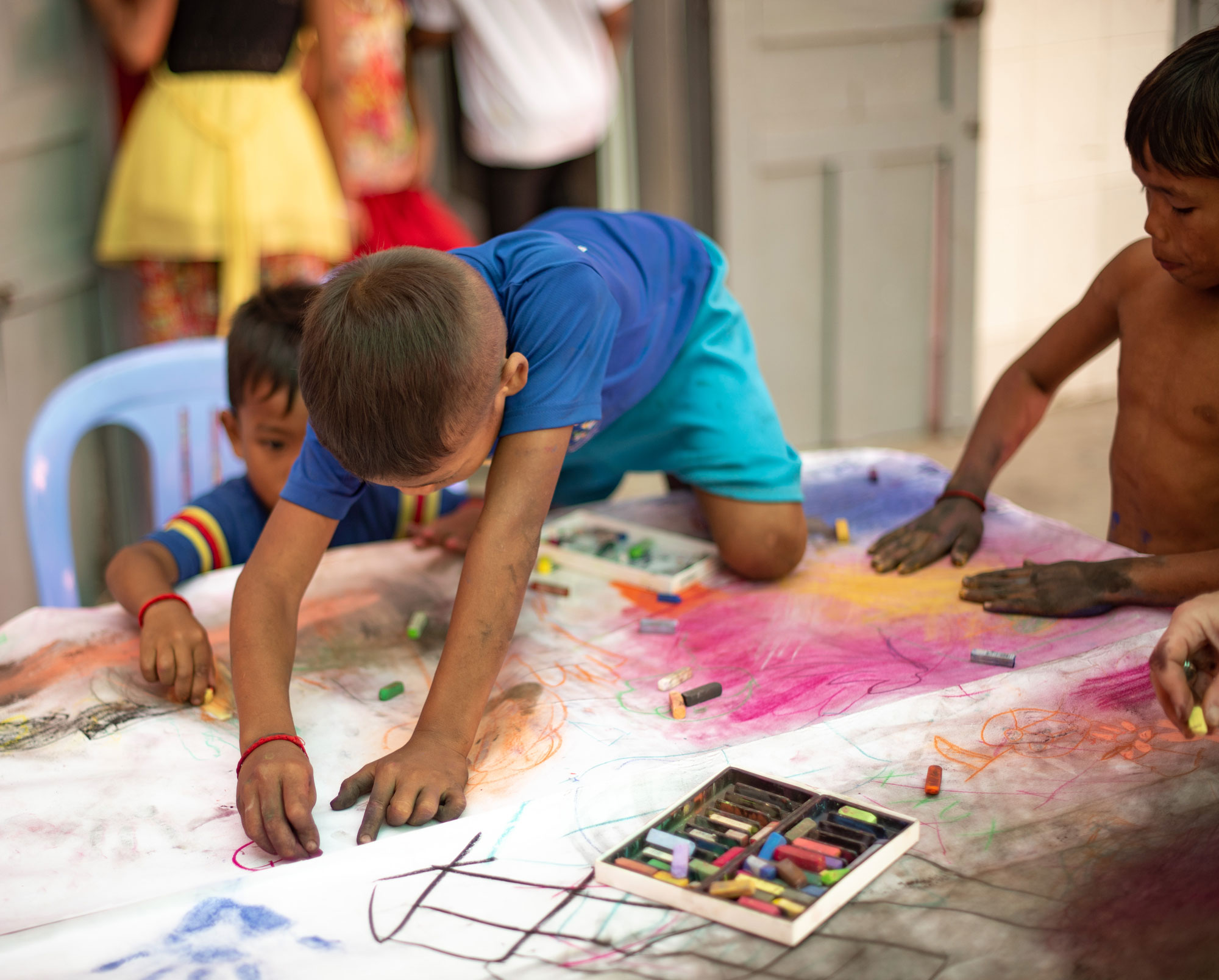 enfant qui dessine à genou sur une table