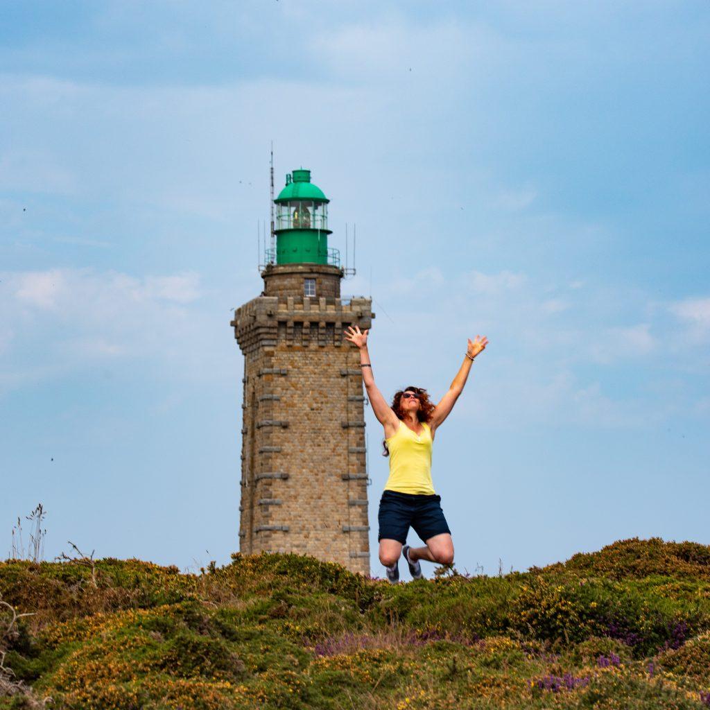 Image d'une femme qui saute de joie devant un phare
