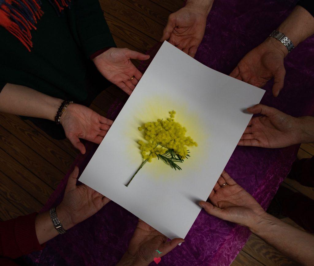 mains soulevant une feuille où est représentée une lumière