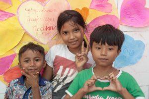 Enfants qui posent devant une fresque colorée